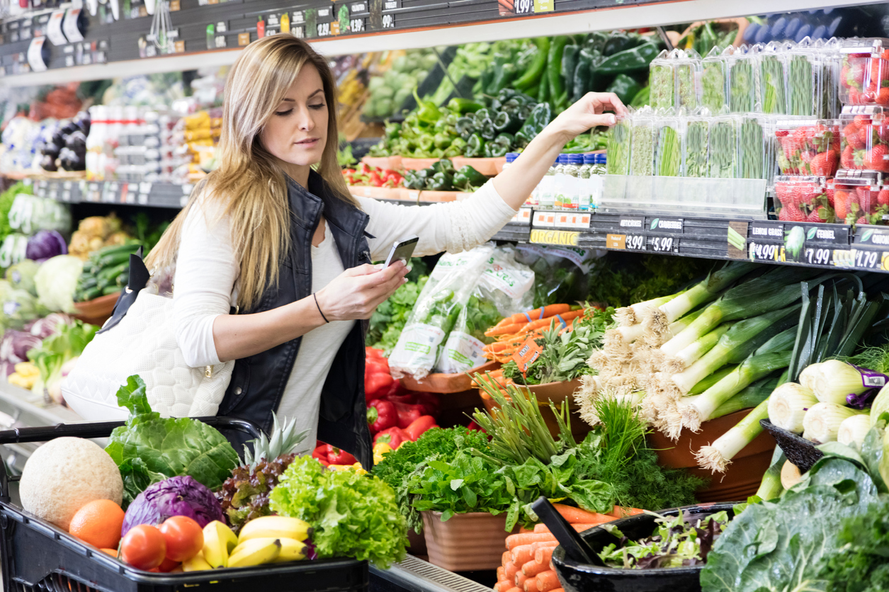 Woman with cart shopping in grocery store in the produce section.